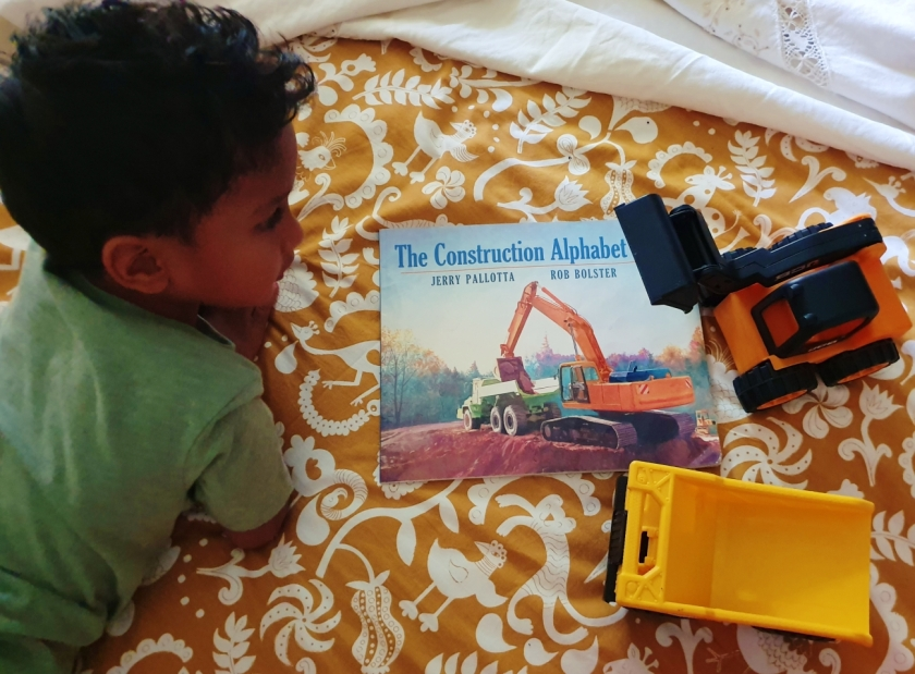 Kid with The Construction alphabet book and construction vehicle toys on the bed