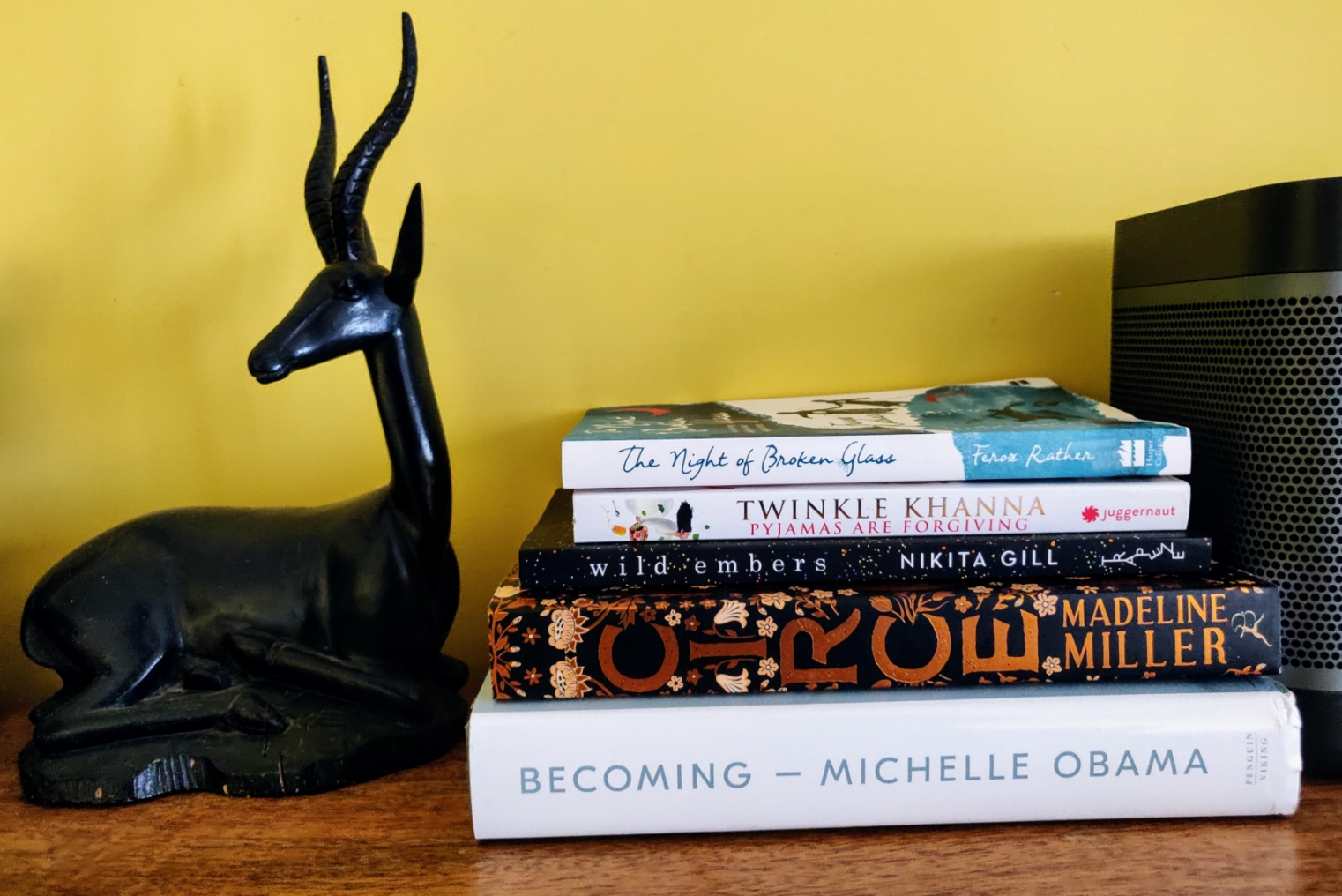 Pile of books next to a small wooden deer