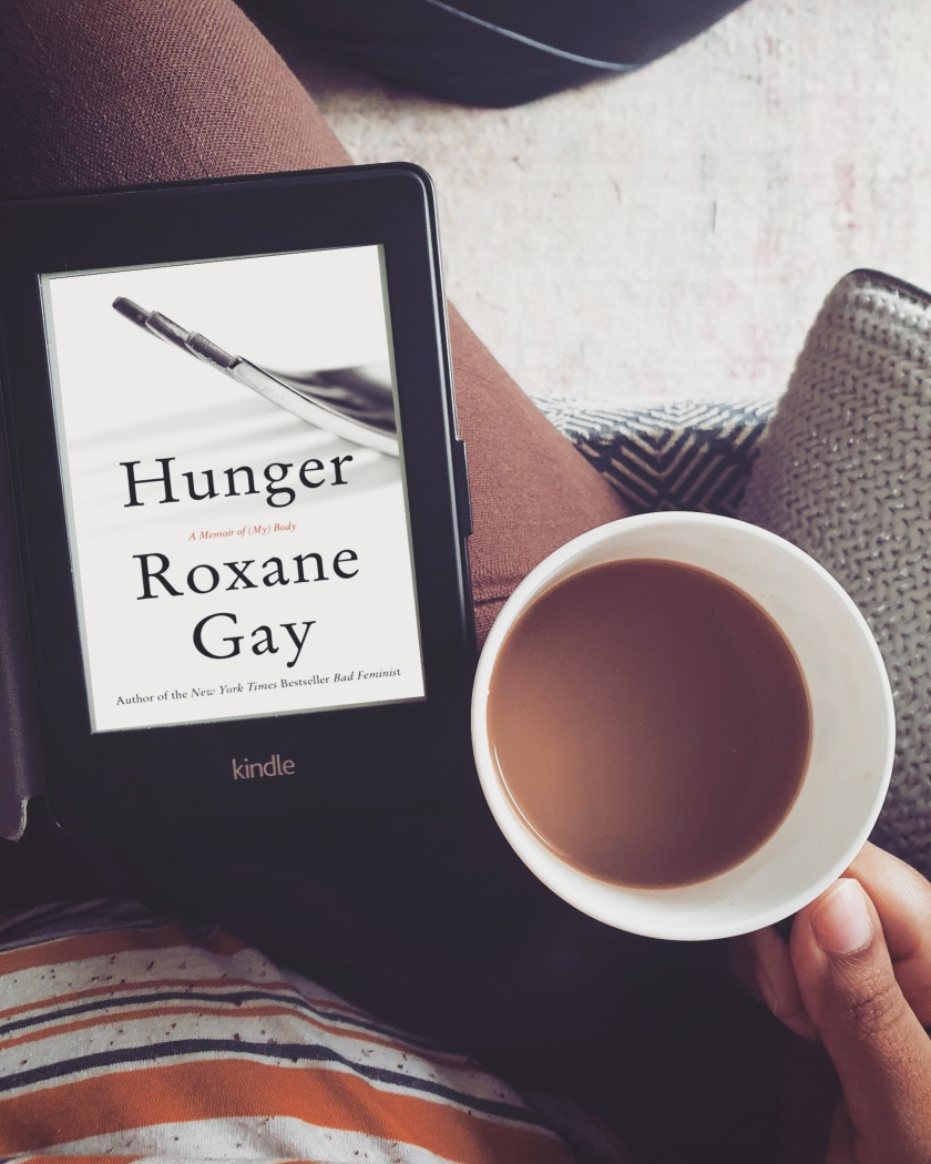 top view of a kindle on a lap with the cover of the book Hunger by Roxane Gay. Person on the sofa is holding a coffee cup next to it