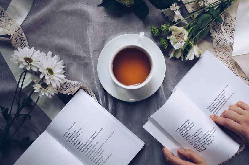 open pages of a book laid next to a tea cup and flowers