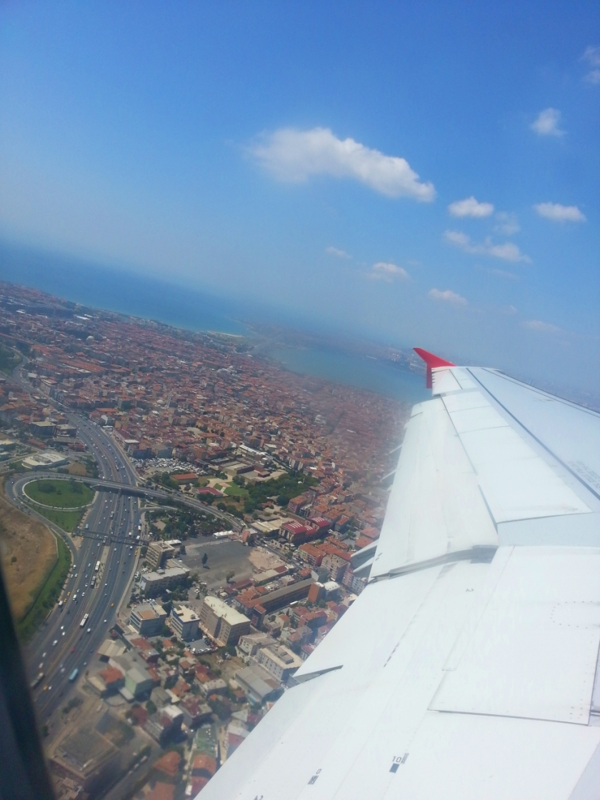 view of the city below from a flying plane with the airplace wing showing