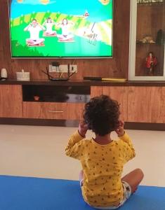 Child following yoga video online