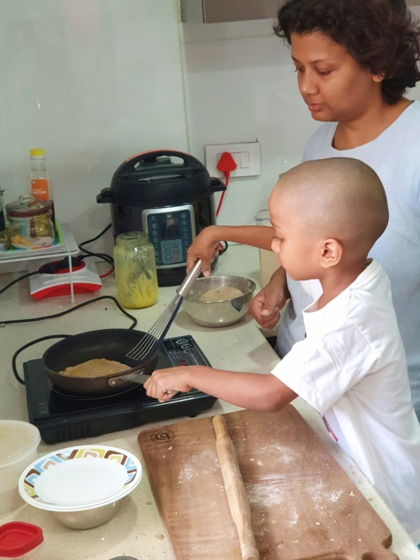 Kid making rotis while his mom supervises