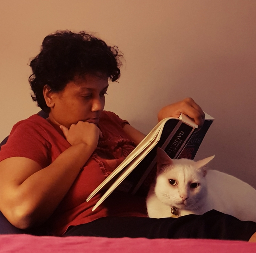 woman on a chair reading a book with a cat on lap