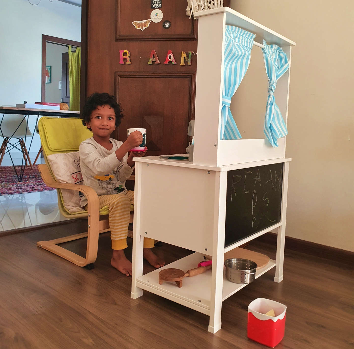 child sitting on a chair in front of his IKEA toy kitchen