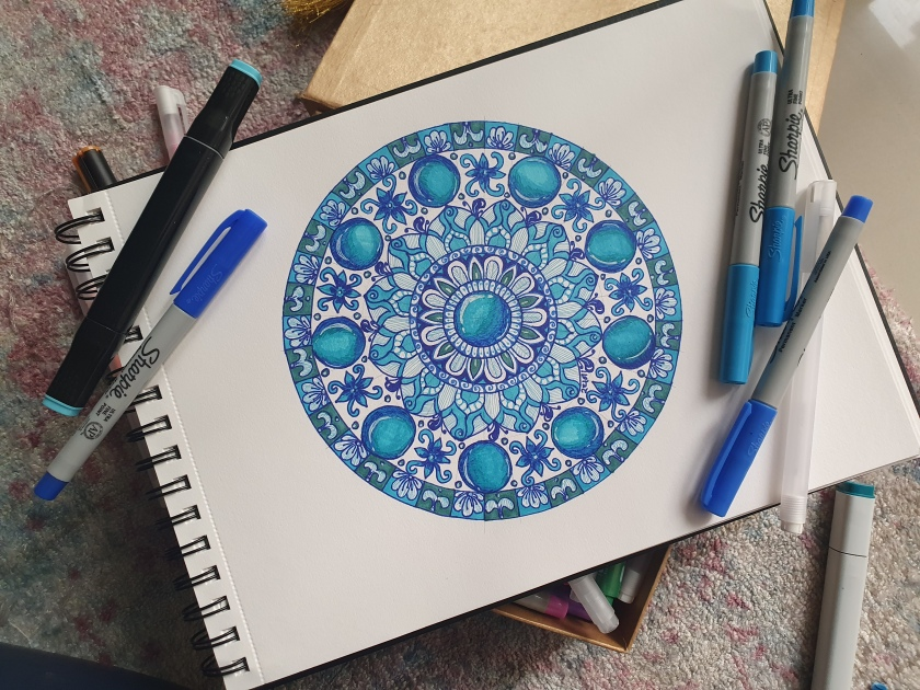A blue theme mandala on a sketchbook with sharpie markers