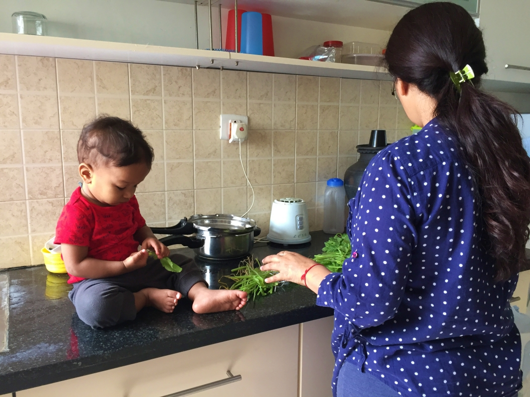 baby sitting on the kitchen counter with a spinach leaf while a woman cleans up a bunch of spinach
