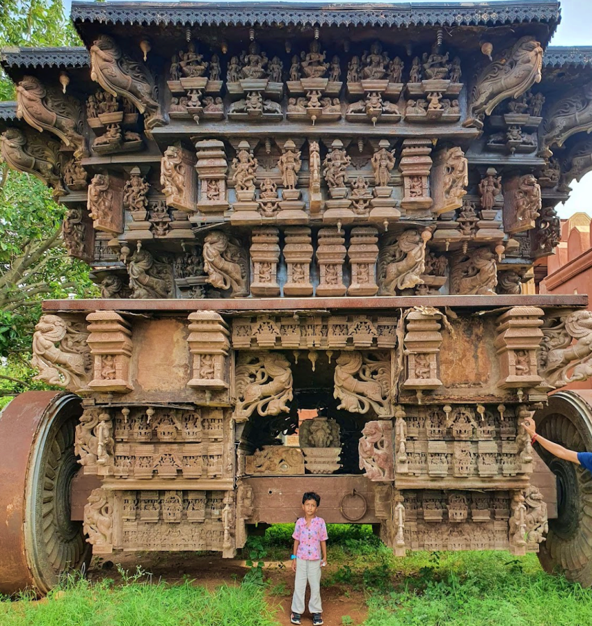Elaborately carved large chariot with a child standing in front
