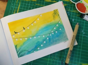 Gouache painting of birds on a wire with art supplies around the art journal sketchbook
