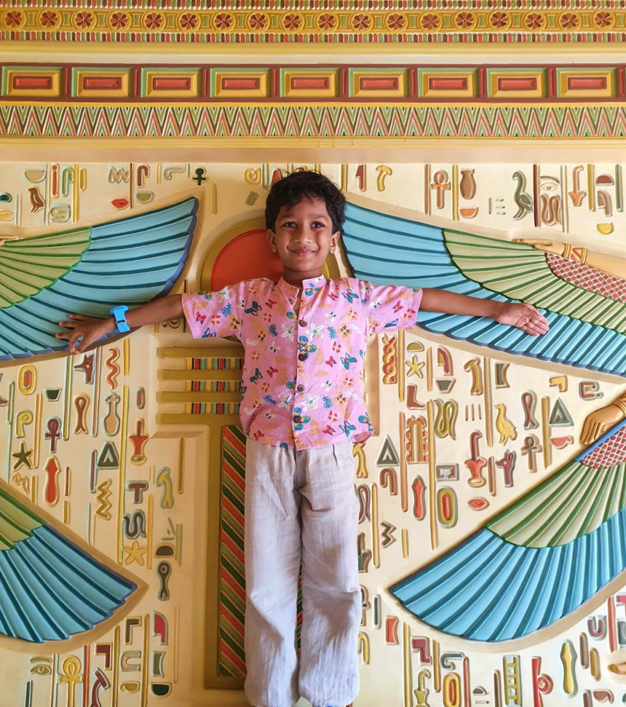 child in pink spreading his arms out in front of a colouful egyptian themed wall panel