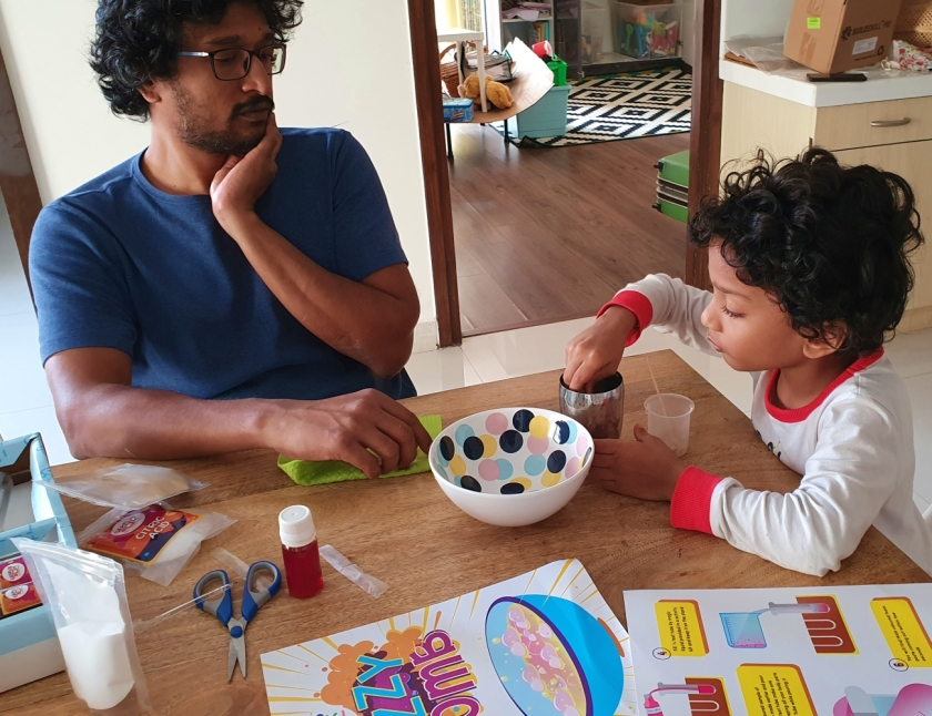 Father and son spending quality time with a science-themed activity box for kids