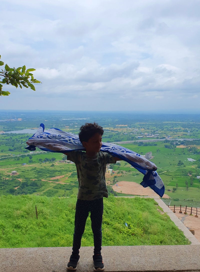 Child with fluttering scarf pretending to fly with the breeze at Bhongir Fort