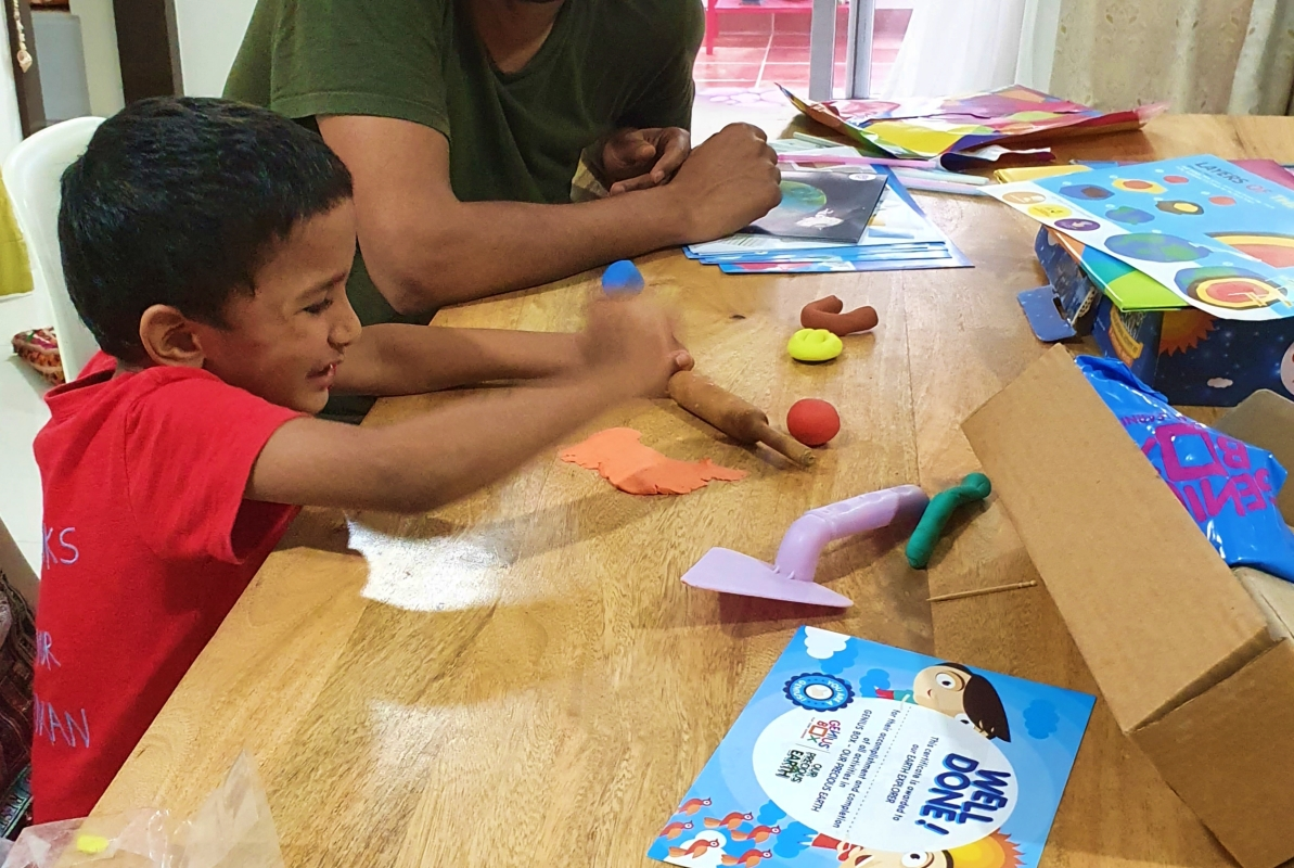 child working on clay activity from the Genius Box activity box