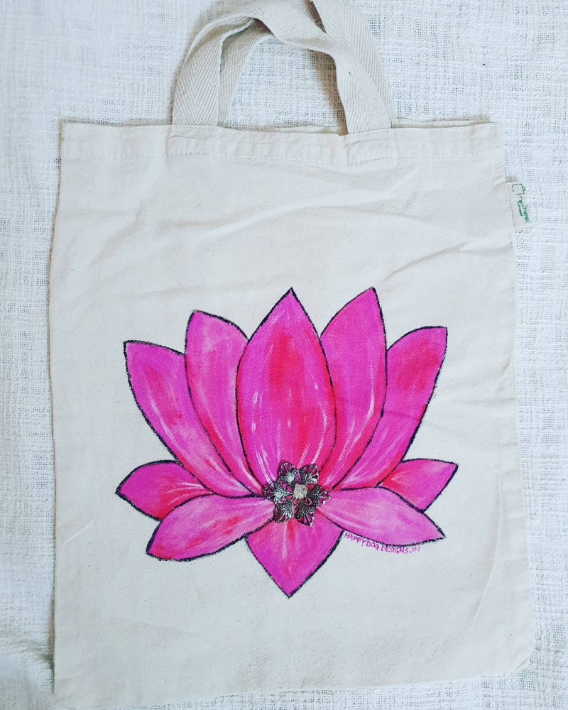 hand painted pink lotus on a white cotton tote bag with a jewelled embellishment