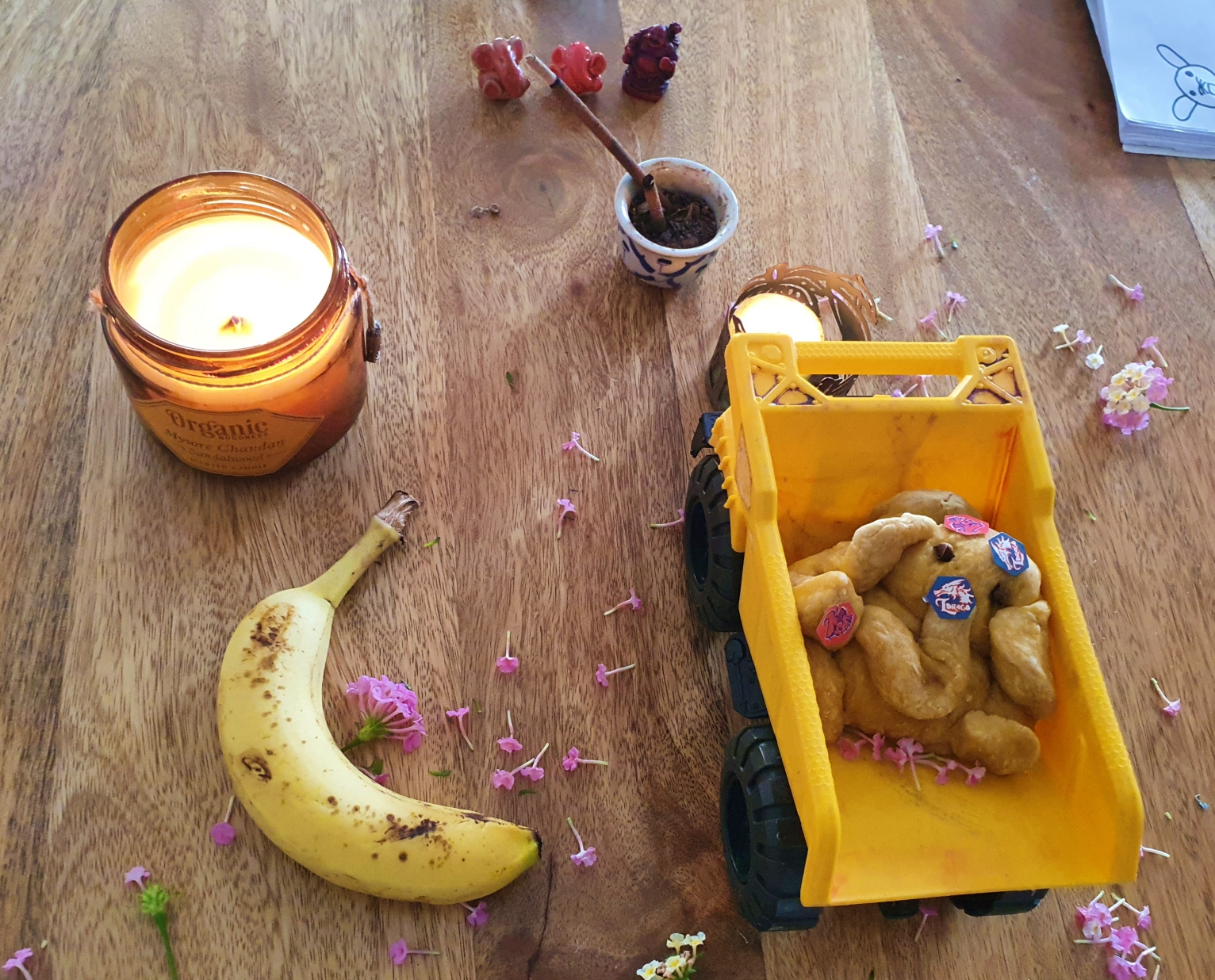Eco friendly Ganesha mandap with flowers, candle, banana and homemade ganesha idol in a kid's toy truck