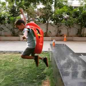Kid wearing a superhero cape jumping from a bench