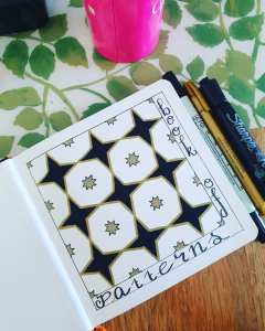Art journal with book of patterns and a simple drawn pattern with pens and markers
