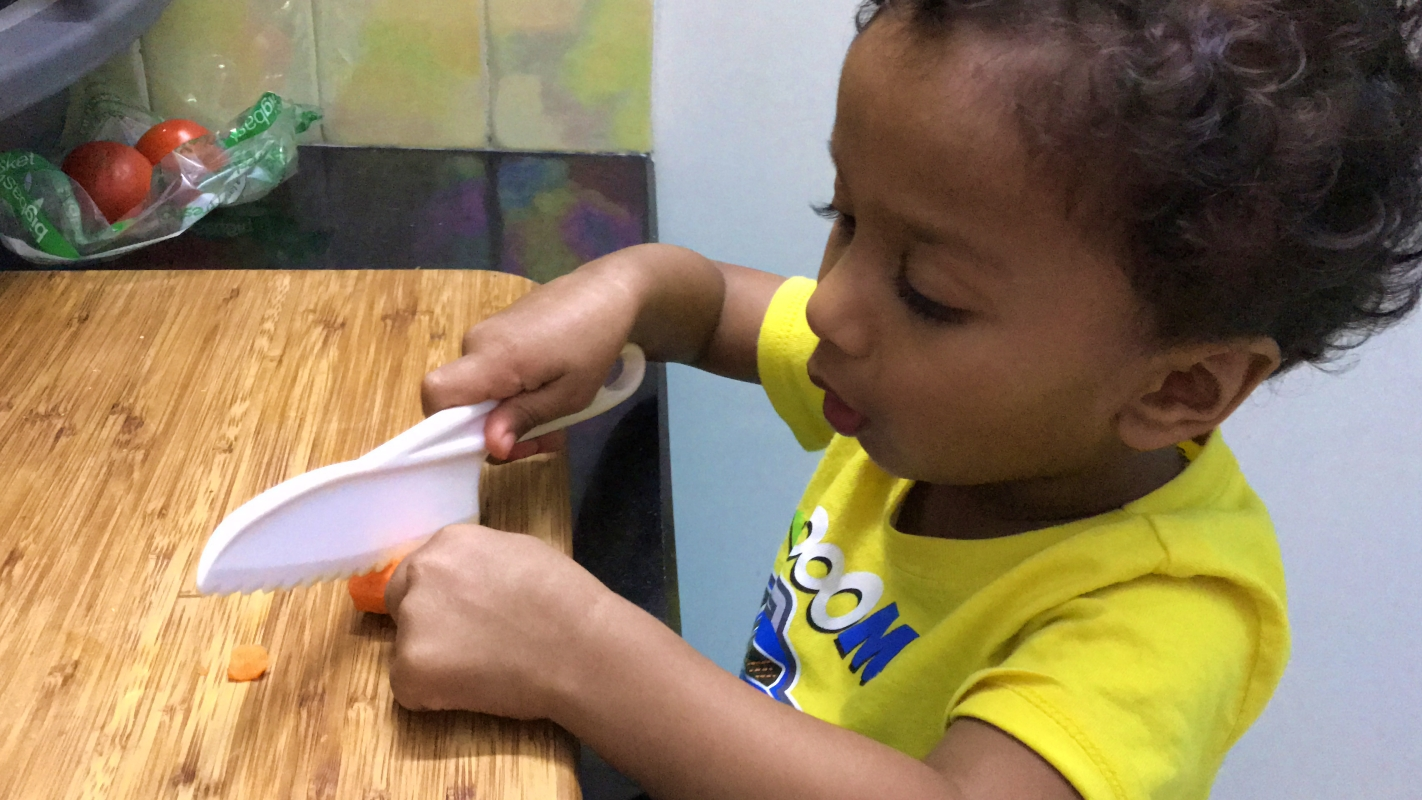 Toddler using a plastic knife to chop a