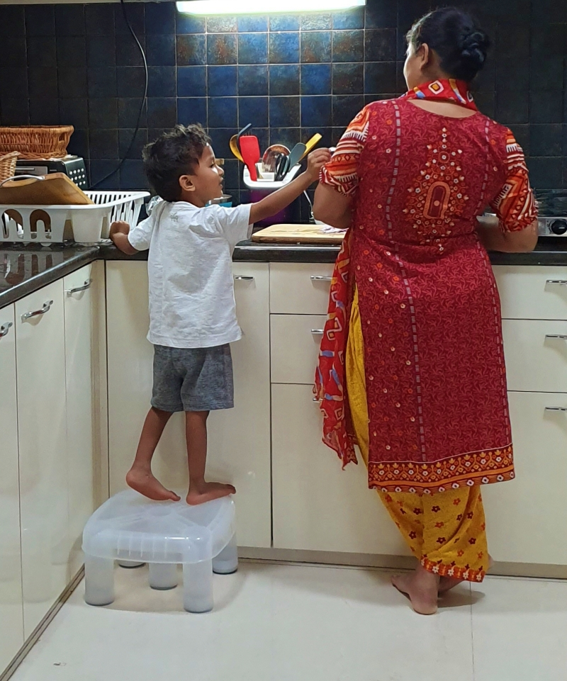 Child enquiring with woman in the kitchen what
