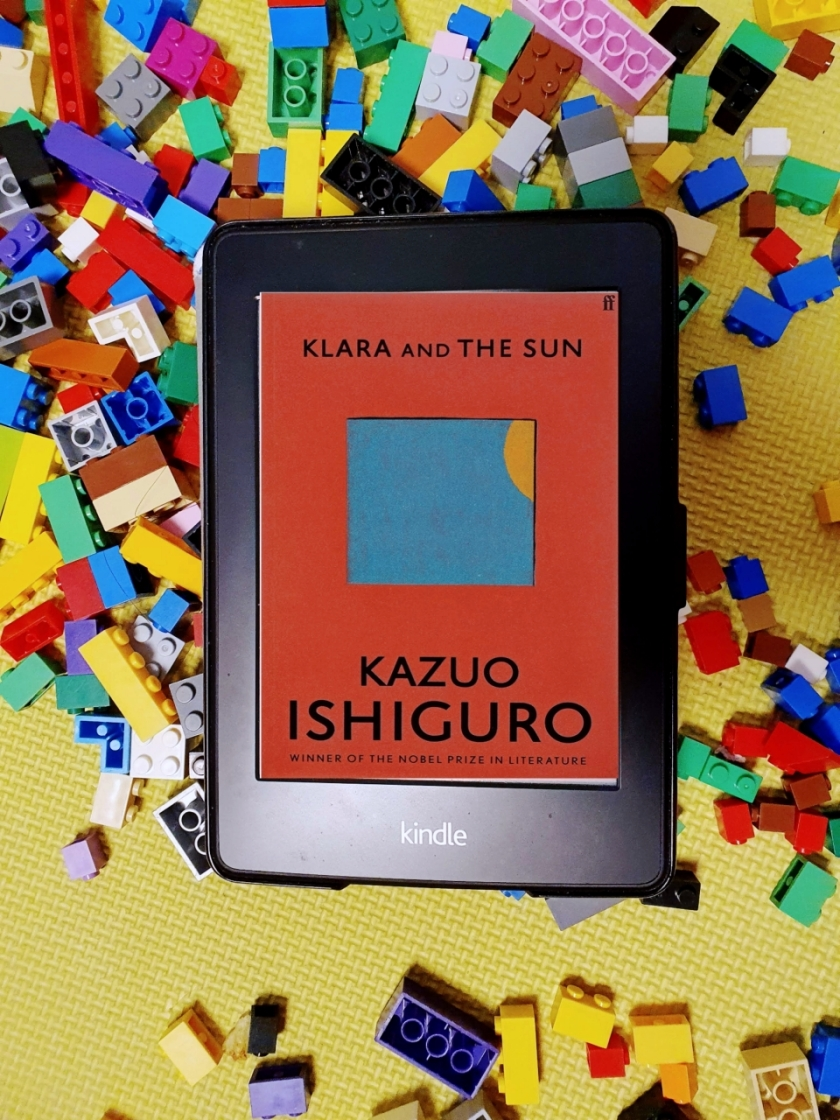 Kindle with the cover of Klara and Sun by Kazuo Ishiguro on a bed of colourful Lego blocks