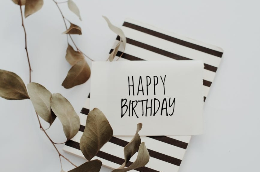 Card saying happy birthday on top of a black and white striped book and a branch of leaves on the side