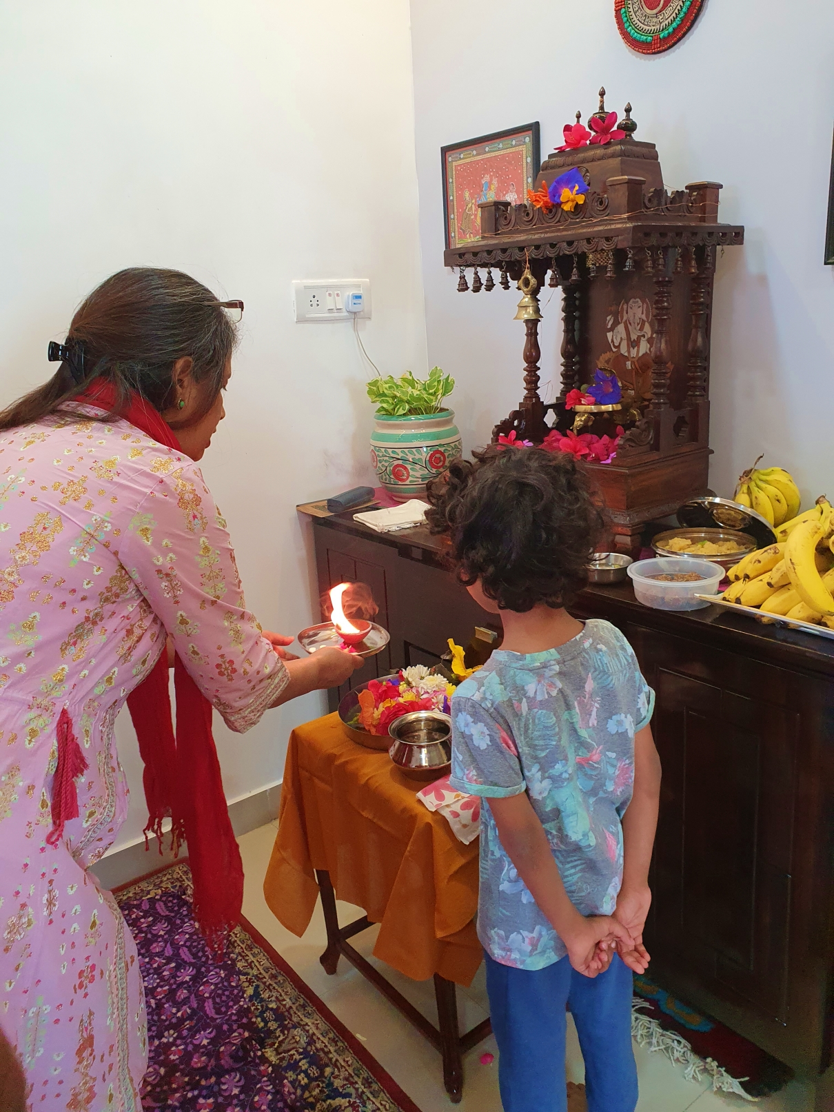 Child learning Hindu religious customs and praying with his grandmother
