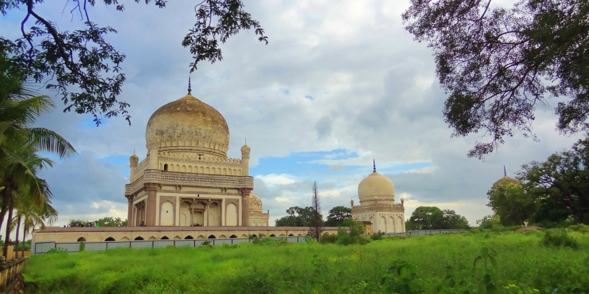 2 of the Qutub shahi tombs with blue skies above and lush greenery all around