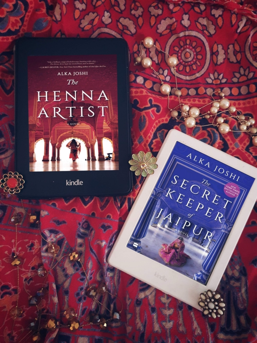 2 kindles with the covers of the books the henna artist and the secret keeper of jaipur, both by Alka Joshi. They're laid out on colourful cloth with jewellery