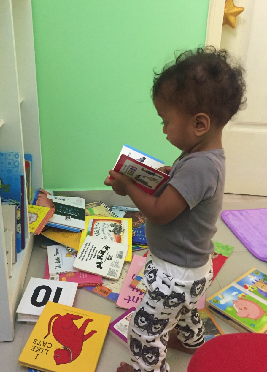 baby reading a book after throwing many books on the floor
