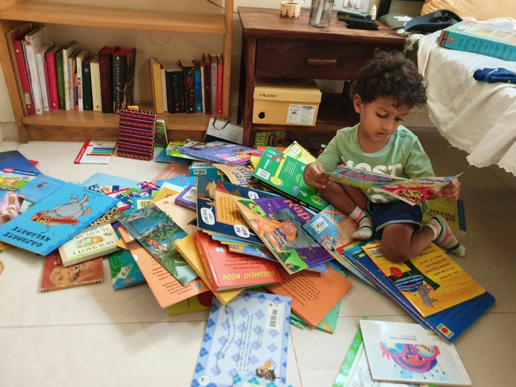 child with a pile of books on the floor