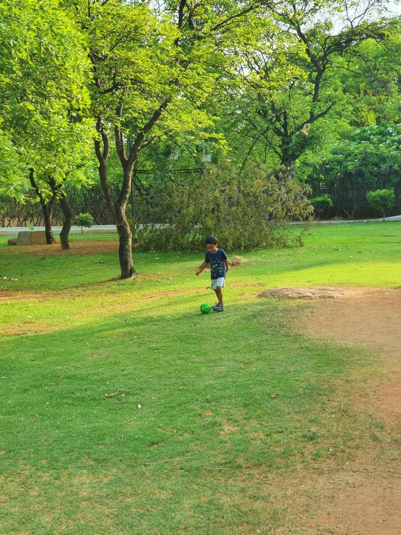 kid kicking a ball around in a park