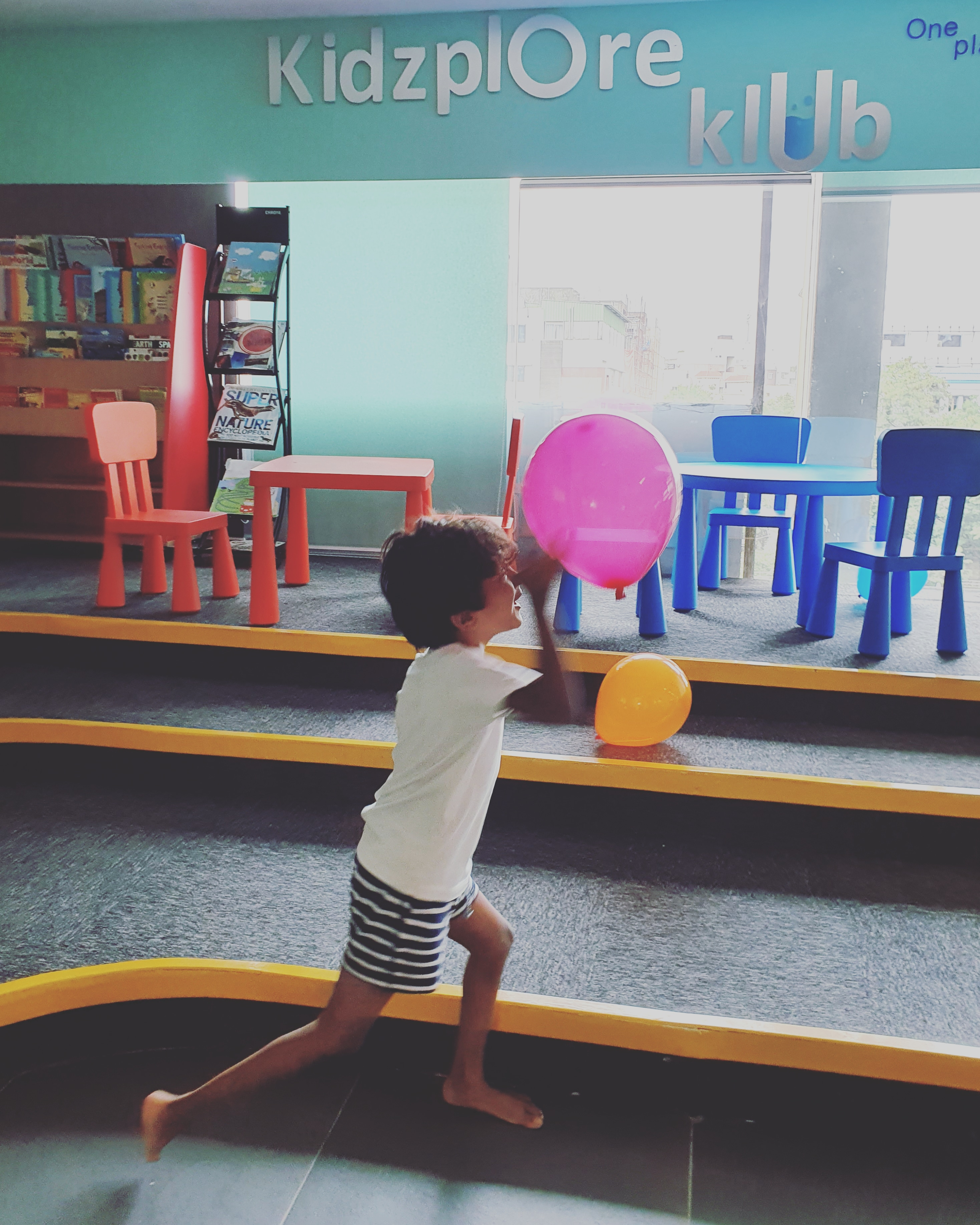 child playing with balloons in an activity centre for kids