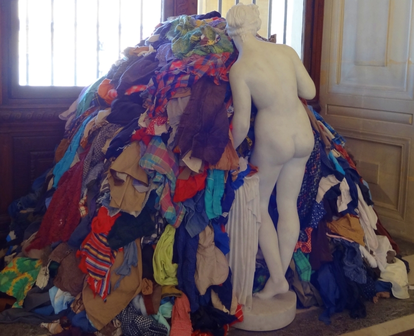 art installation at the Louvre paris of a woman with a large pile of clothes