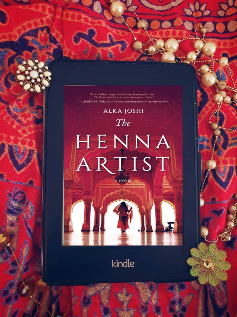 Kindle Paperwhite displaying cover of the henna artist laid on a bright red cloth with jewellery