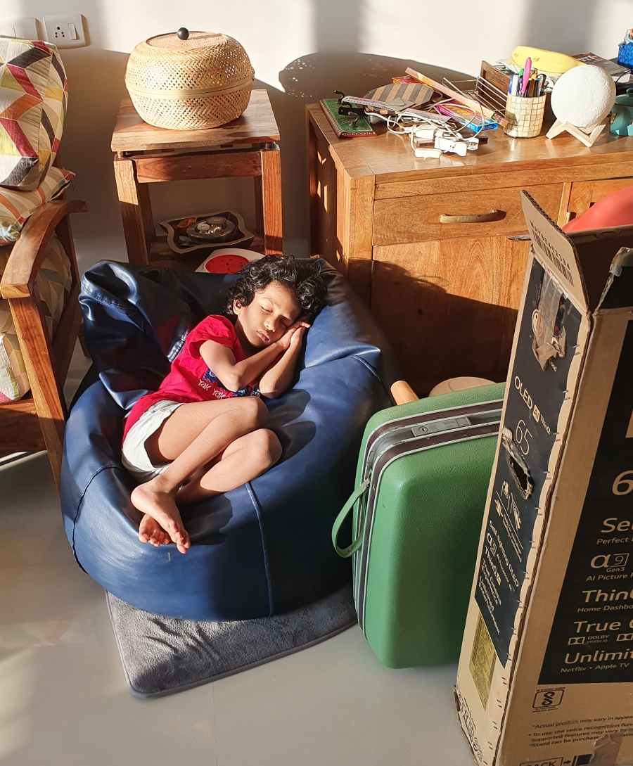tired baby sleeping on a beanbag amidst unpacked boxes